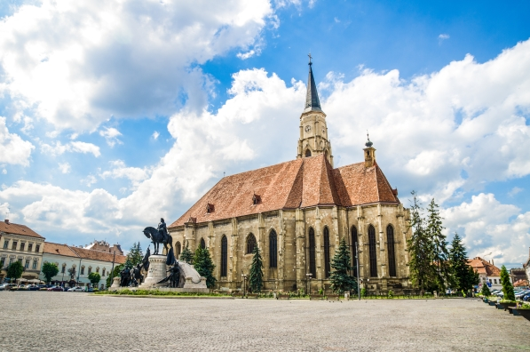 Cluj Napoca Unirii Square with the medieval gothic St Michael Church and the statue of Matei Corvin or Matias